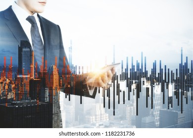 Businessman using tablet on abstract city background with forex chart. Technology and trade concept. Double exposure