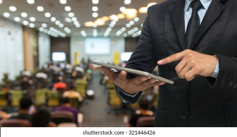 Businessman using the tablet on the Abstract blurred photo of conference hall or seminar room with attendee background