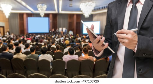 Businessman using the tablet on the Abstract blurred photo of conference hall or seminar room with attendee background, Business meeting concept