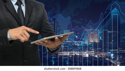 businessman using the tablet on Trading graph on the cityscape at night and world map background,Business financial concept