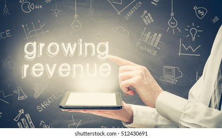 Businessman is using tablet pc and selecting growing revenue.