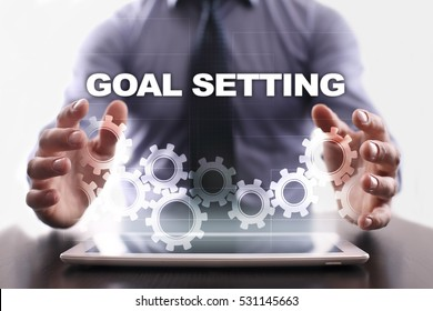 Businessman is using tablet pc and selecting goal setting.