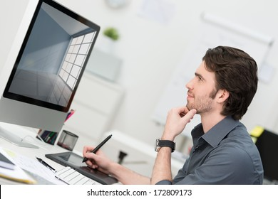 Businessman using a tablet and pen to navigate on his desktop computer in the office sitting in profile thinking and reading the monitor