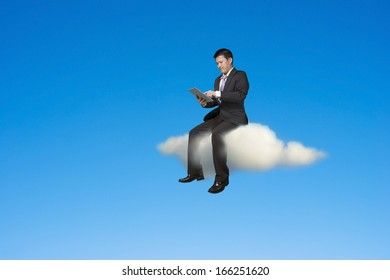 Businessman using tablet and sitting on cloud in sky background