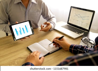 Businessman using tablet to teach and  analysis the situation on the market value , Business concept