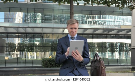 Businessman Using Tablet while Sitting Outside Office