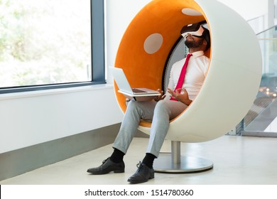 Businessman using virtual reality simulator for meditating. Man in office clothes and VR headset sitting in interactive chair with laptop and making zen gesture with hands. Meditation concept