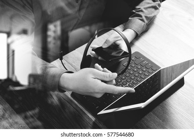 businessman using VOIP headset with digital tablet computer and smart phone,concept communication and call center and customer service help desk,black and white