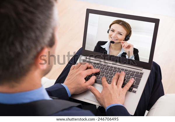 Businessman Video Chatting With Businesswoman On Laptop