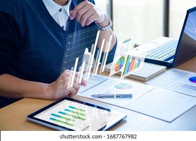 Businessman con gráficos de realidad virtual está revisando profundamente los informes financieros para obtener un retorno sobre la inversión, el ROI o el análisis de riesgo de inversión.