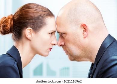 Businessman vs businesswoman head to head office confrontation