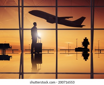 Businessman Waiting In An Airport Lounge With A Scenery Of Departing Airplane
