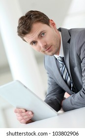 Businessman waiting in hallway with electronic tablet
