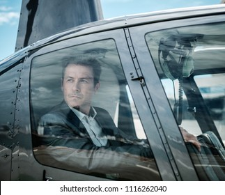 Businessman waiting inside private helicopter