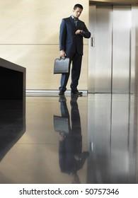 Businessman Waiting in Lobby checking wristwatch