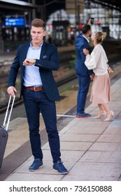 businessman waiting for the train and a couple in the background