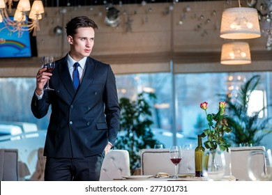 Businessman waits for the main meeting. Young man businessman in formal wear standing in a restaurant while holding a glass of wine and looking at the camera