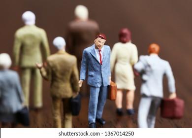 A businessman walking against crowd.