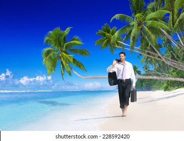 Businessman walking along the beach.