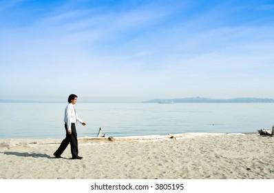 A businessman walking along the beach alone