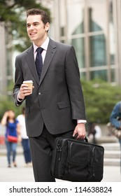 Businessman Walking Along Street Holding Takeaway Coffee