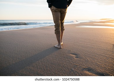 Businessman walking bare foot on sandy beach near the sea, after work.