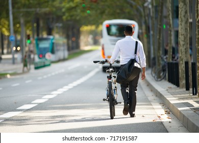 Businessman Walking with Bike in Street After Work