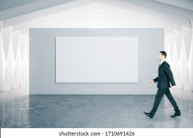 Businessman walking and  blank poster in modern gallery interior. Art and design concept.