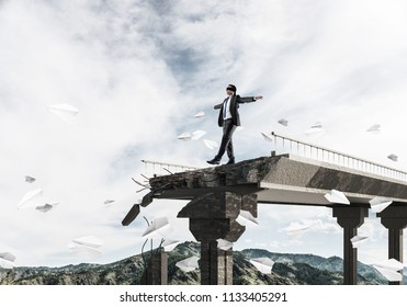 Businessman walking blindfolded among flying paper planes on concrete bridge with huge gap as symbol of hidden threats and risks. Skyscape and nature view on background. 3D rendering.