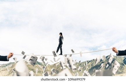 Businessman walking blindfolded on rope among flying documents and above high mountains as symbol of hidden threats and support. Nature view on background.