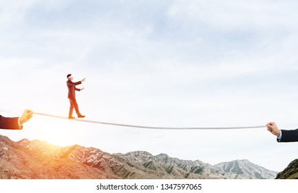 Businessman walking blindfolded on rope above high mountains as symbol of hidden threats and support. Skyscape and nature view on background.
