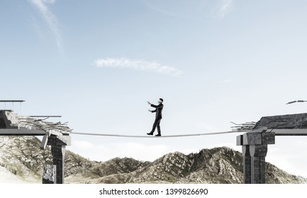 Businessman walking blindfolded on rope above huge gap in bridge as symbol of hidden threats and risks. Skyscape and nature view on background. 3D rendering.
