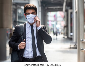 Businessman walking in city with very small amount of people during covid-19 outbreak make phone call and wearing white mask
