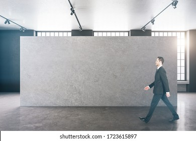 Businessman walking in clean gallery interior with copy space on green wall. Presentation concept. Mock up, 3D Rendering