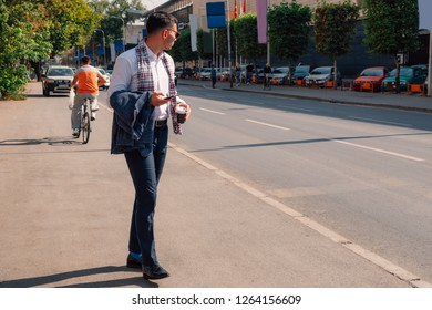 Businessman is walking down the street on a sunny day, holding coffee in his hands and talking on mobile.