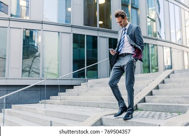 businessman walking downstairs in an office park with a tablet in the hand