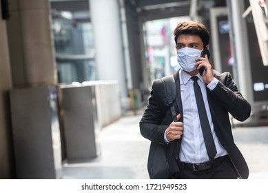 Businessman walking in an empty city during covid-19 outbreak make phone call and wearing white mask