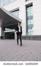 Businessman walking in front of an office building