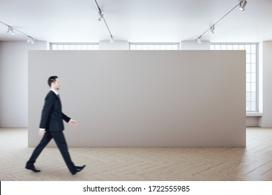 Businessman walking in gallery room with copy space on green wall. Presentation concept. Mock up, 3D Rendering