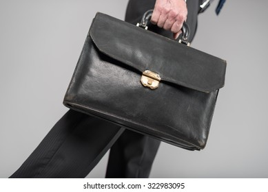 Businessman walking with his briefcase on grey background