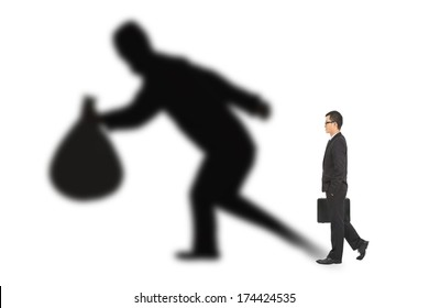 businessman walking and holding bag  with thief shadow