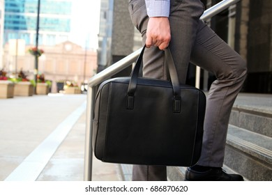 Businessman walking and holding  a  leather briefcase in his hands Modern city behind