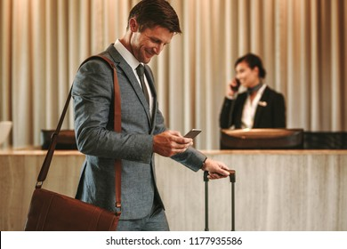 Businessman walking in hotel lobby with suitcase and using his smart phone. Male business traveler in hotel hallway with cellphone and luggage.