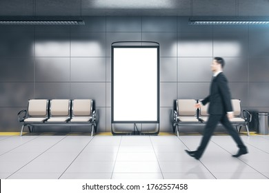 Businessman walking in metro station with blank poster on wall. Underground and urban concept. Mock up