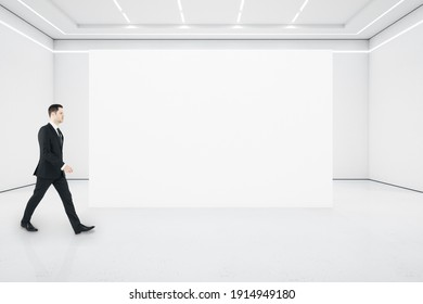 Businessman walking in minimalistic gallery interior with empty presentation wall. Art and design concept. Mock up.