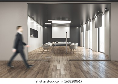 Businessman walking in modern conference room with blank tv screen on wall. Workplace and corporate concept.