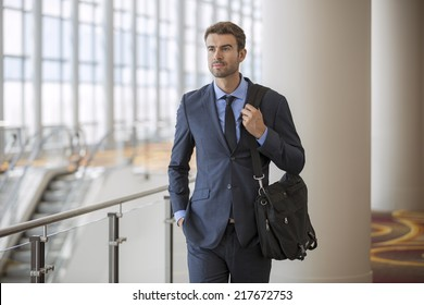 Businessman walking in the office corridor with briefcase