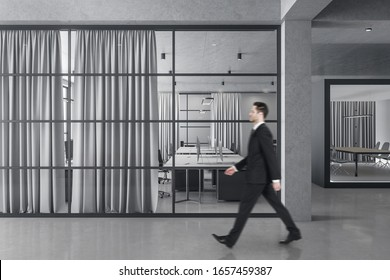 Businessman walking in office interior with computers and curtains. Occupation and worker concept.