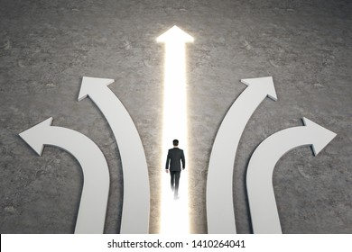 Businessman walking on abstract white and glowing arrows on concrete background. Different direction and success concept.