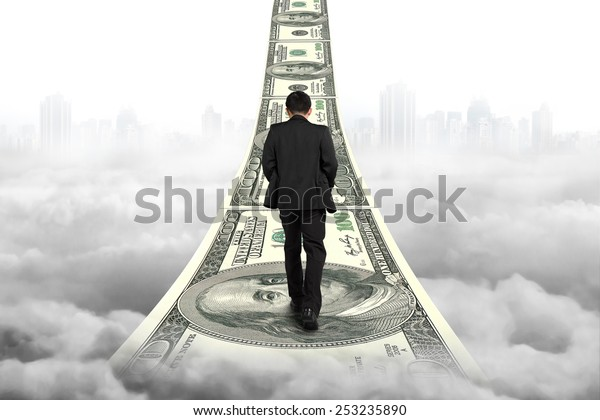 Businessman walking on the money stairs with gray cityscape cloudscape background